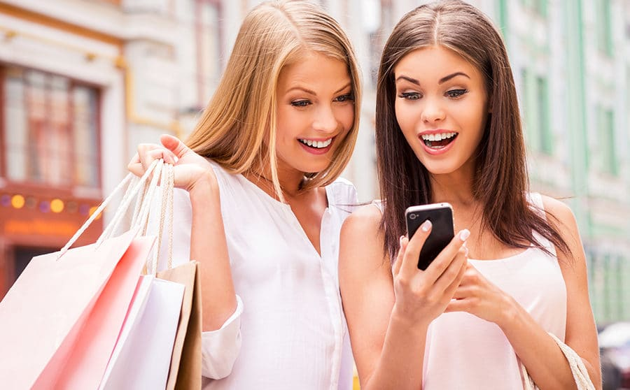 Two surprised young women holding shopping bags and looking at mobile phone together while standing outdoors